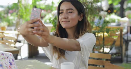 изображение : Young woman at an outdoor restaurant table taking a selfie on her mobile phone with a quiet pleased smile Стоковые видеозаписи
