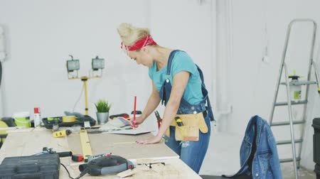 kontrplâk : Side view of young blond woman in jeans overalls and tool belt bending over wooden workbench drawing lines with pencil on plywood surrounded by instruments in workshop.