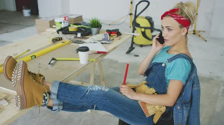 macacão : Relaxed young blond woman in jeans overalls sitting relaxed with legs on workbench with instruments talking on mobile phone and looking away
