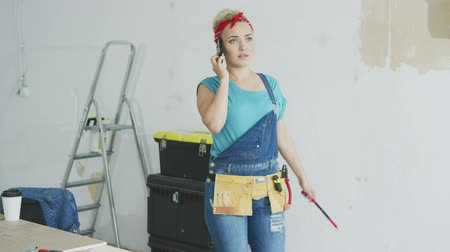 macacão : Worried attractive young female in jeans overalls standing at white unpainted wall with instruments and talking on mobile phone looking away and waving hand with pencil.