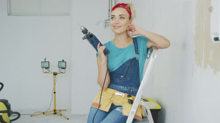 saç bantı : Cheerful young blond female in jeans overalls and carpenter tool belt sitting with electric drill on stepladder and looking at camera smiling and touching neck with unpainted wall on background. Stok Video