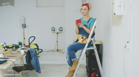 rüya gibi : Attractive young blond woman in jeans overalls, tool belt and red headband sitting relaxed on stepladder holding red mug with drink and looking away dreamily at unpainted wall and workbench
