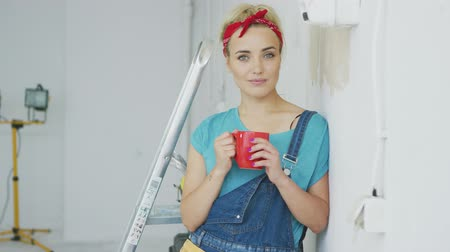 hajló : Beautiful blond woman in jeans overalls and red headband standing relaxed with mug of hot drink leaning on shoulder against white unpainted wall and looking at camera smiling. Stock mozgókép