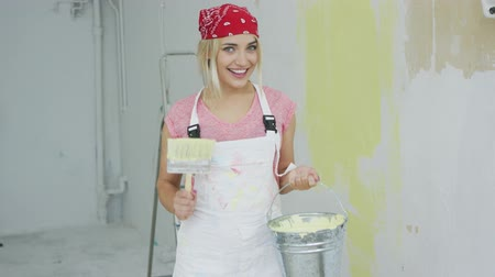 megújít : Young female in white overalls and red bandana on head standing with brush and bucket of yellow wall paint in hands smiling and looking at camera with stepladder and plastered wall on background. Stock mozgókép