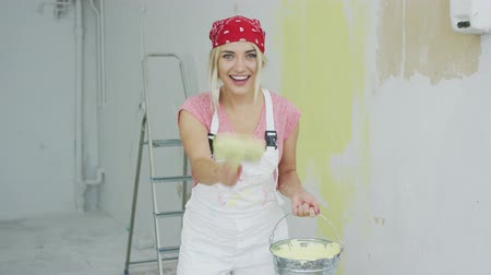 macacão : Happy energetic young blond woman in bandana and white overalls holding bucket with pastel yellow wall paint and stretching out hand with brush looking at camera smiling and biting lip.