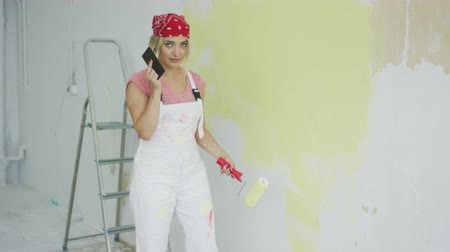 ručně malovaná : Side view of young blond female in white overalls and red bandana painting plastered wall pastel yellow with roller and talking on mobile phone in hand.