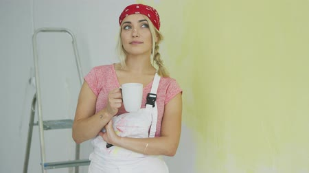 wistful : Beautiful young wistful woman in pink shirt and white overalls standing relaxed at half-painted pastel yellow wall and holding white mug with beverage looking up. Stock Footage