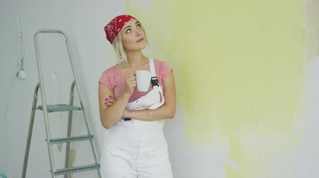 wistful : Cute young blond female in white overalls and bandana holding white cup with beverage standing at half-painted pastel yellow wall at stepladder and looking up wistfully smiling.