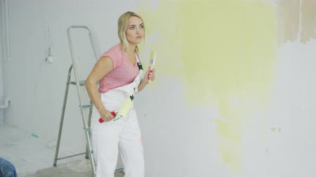 élénk : Beautiful happy young blond woman in white overalls with paint roller dancing in room under repair and looking away with stepladder and white half-painted wall on background.