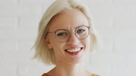 vidro : Beautiful young female with short blond hair wearing glasses and looking at camera while standing on white background