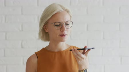 rövid : Attractive young woman with short blond hair and stylish glasses talking while standing on background of white brick wall and recording audio message on smartphone Stock mozgókép