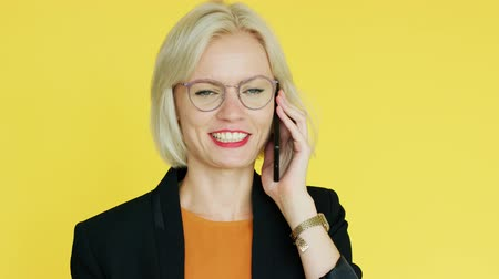 yellow jacket : Attractive young lady in elegant outfit and glasses smiling and speaking on phone while standing on bright yellow background Stock Footage