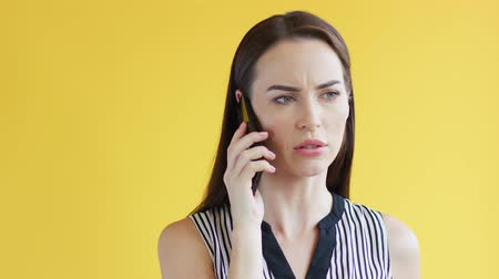 хмурый : Beautiful young female in striped clothing frowning and talking on smartphone while standing on bright yellow background