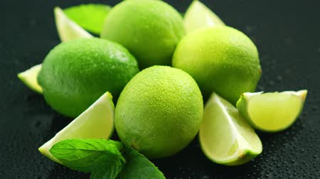 servido : Closeup fresh bright green limes placed on dark background with water drops