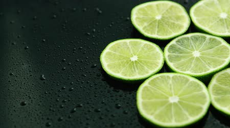cseppfolyósítás : From above slices of fresh green sour lime on dark table with water drops Stock mozgókép