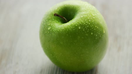 промывали : Closeup shot of green wet apple placed on light wooden background