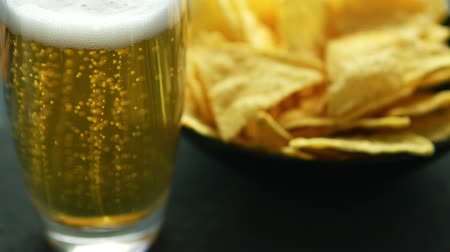 ale : Transparent glass of light beer with foam and bowl of crispy golden nacho chips served on table