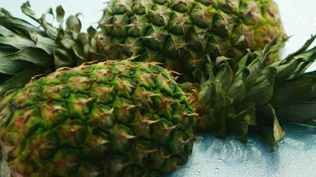 unpeeled : From above shot of cut halves of fresh pineapples with green leaves lying on blue surface