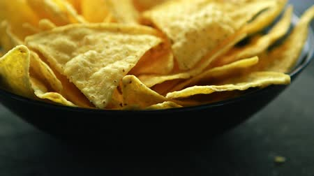 servido : Closeup shot of bowl filled with crispy golden nacho chips and served on table in daylight