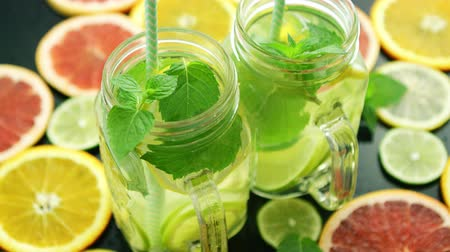 infused water : From above shot of few glass jars filled with lime lemonade and mint leaves composed on table among slices of citrus fruit