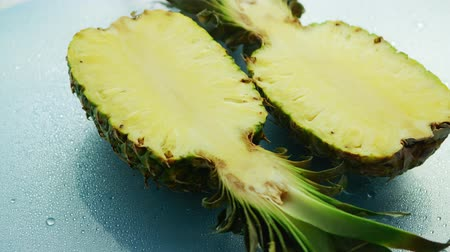 unpeeled : From above shot of ripe yellow halves of sweet pineapple served on wet glass surface