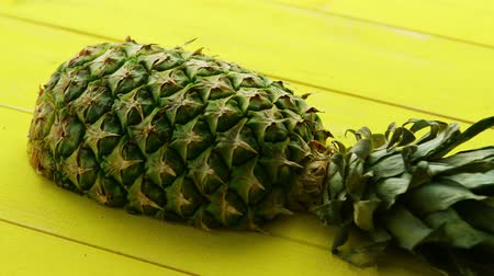 unpeeled : Cut half of unpeeled pineapple with green leaves lying on bright wooden panels of yellow color