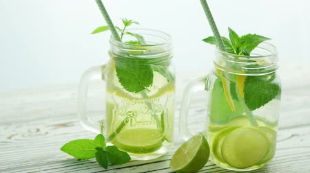 infused water : Few glass jar cups with green straws and fresh lemonade with lime slices and green mint served on wooden table