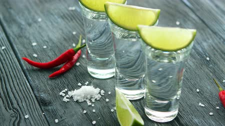 few : Served glass shots filled with tequila and slices of lime on wooden table with heap of salt and chili pepper Stock Footage