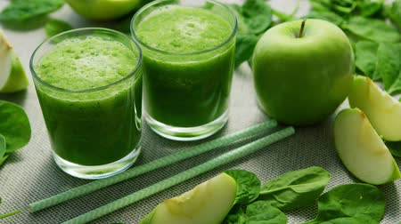 servido : Layout of few glasses filled with green smoothie and served on table with green apples and spinach leaves