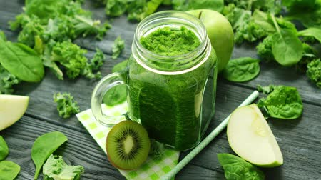 juice jar : From above shot of green smoothie in glass composed on table with green apple and spinach leaves with kiwi