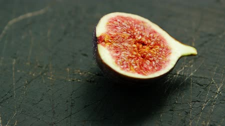 yarım uzunluk : Closeup shot of cut half of delicious fig with red ripe flesh and seeds on rough wood surface