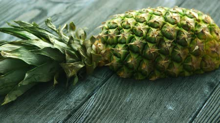 juicy : From above shot of unpeeled pineapple half with green leaves lying on wooden table Stock Footage