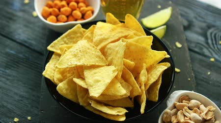 picante : From above shot of composed bowl with crispy nacho chips on board with salty nuts for party snack