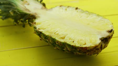 ve slupce : Closeup of juicy and ripe half of cut pineapple of bright yellow color lying on vivid wooden panels