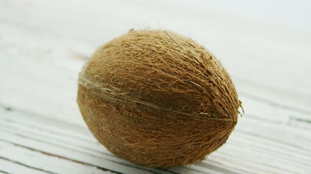 unpeeled : Closeup of textured unpeeled coconut in brown shell lying on white wooden table in soft daylight