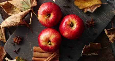 fragrância : From above shot of layout of shiny ripe apples with autumnal leaves and aromatic cinnamon sticks in daylight