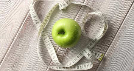 сантиметр : From above shot of composed green fresh apple and measuring tape for weight loss concept on top of wooden table Стоковые видеозаписи