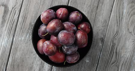 beslenme : Top view of round bowl filled with ripe wet purple plums and served on gray wooden table Stok Video