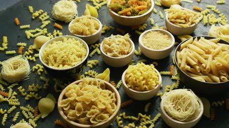 сортировать : From above view of different uncooked macaroni placed in white bowls on gray background