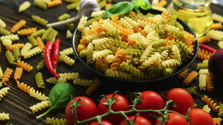makaróni : From above view of black bowl full of spiral macaroni of different color with fresh tomatoes laid near on wooden background