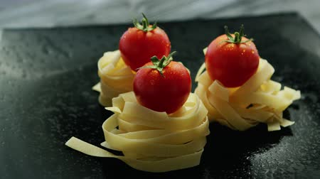 benzer : From above view of rolled tagliatelle with fresh tomatoes on top placed on gray table with drops on surface