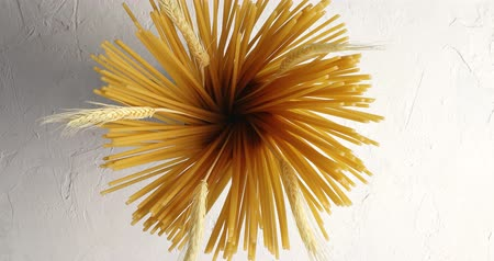 disposição : From above view of bunch of uncooked pasta decorated with twigs of wheat on white background