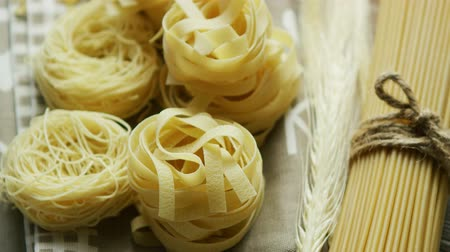 лапша : From above view of spaghetti rolled in balls with raw macaroni laid near and tied with rope Стоковые видеозаписи