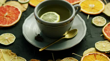 limão : From above view of cup of hot tea with slice of lemon and spoon decorated with dry leaves and pieces of orange and lime on gray background.