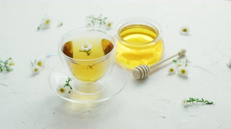 herbata : Transparent glass cup with herbal camomile tea and fresh flowers on table with jar of honey and wood stick