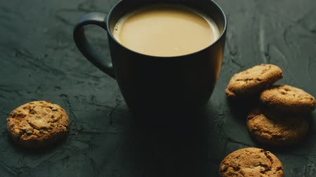 sugar cookies : Closeup of black mug with cacao on black table with heap of delicious sweet biscuits Stock Footage