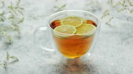 toalha de mesa : From above view of glass mug with brown tea and lemon on white background of tablecloth Stock Footage