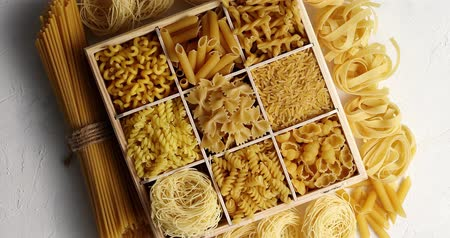 лапша : From above view of macaroni of different sort placed in dish with sections on white background Стоковые видеозаписи