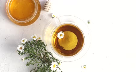 toalha de mesa : From above view of glass cup of tea and bowl of honey decorated with flowers of camomile on white background Stock Footage