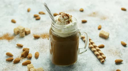 çırpılmış : Glass jar with sweet caramel drink garnished with whipped cream and served with straw on table among nuts